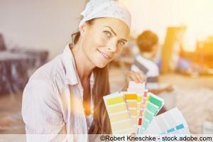 Frau als Heimwerker mit Auswahl an Wandfarbe